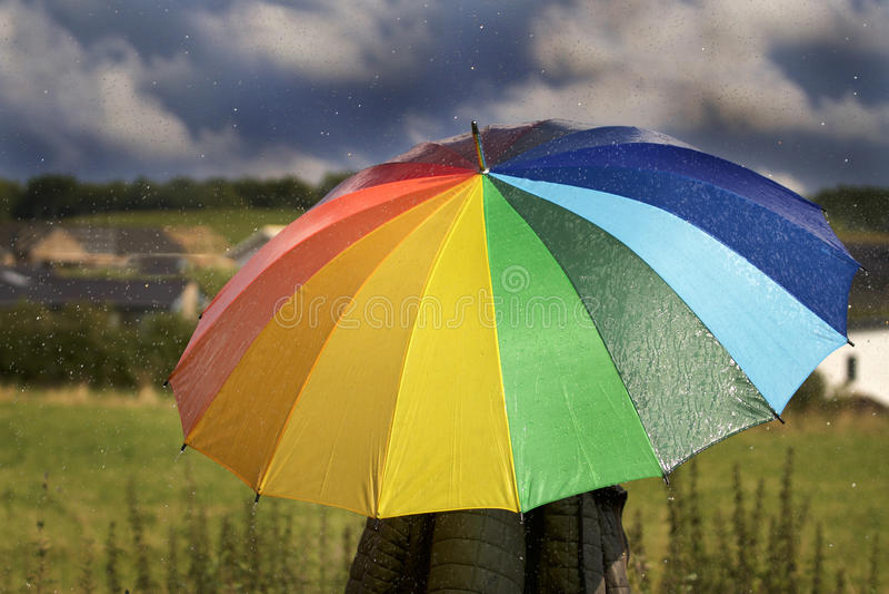 Een persoon met regenboog kleurde paraplu in de regen stock foto
