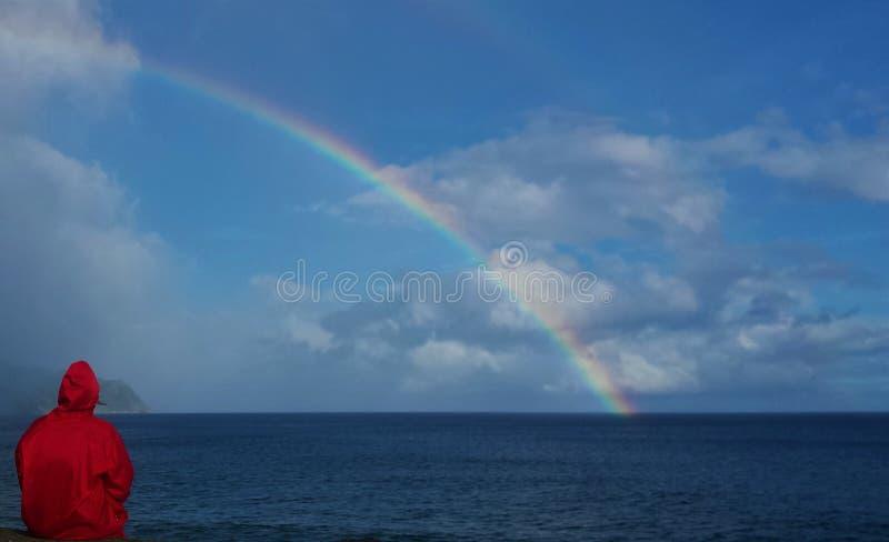 Een persoon met een regenjas die de regenboog bekijken royalty-vrije stock foto's
