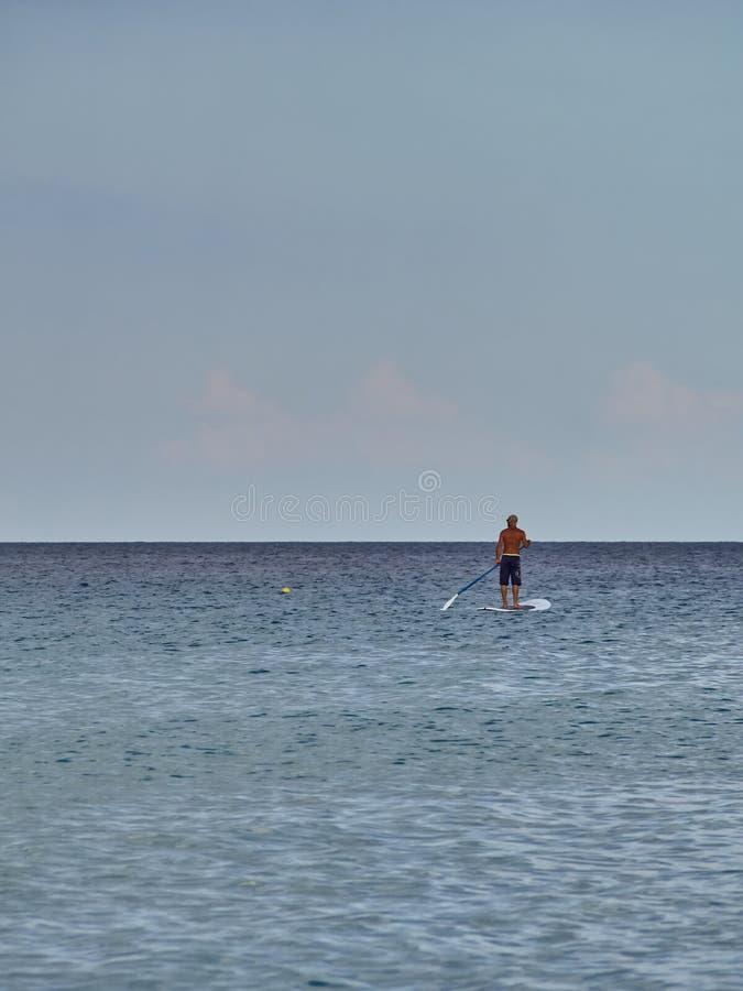 Een persoon oefent branding dichtbij het strand uit royalty-vrije stock foto