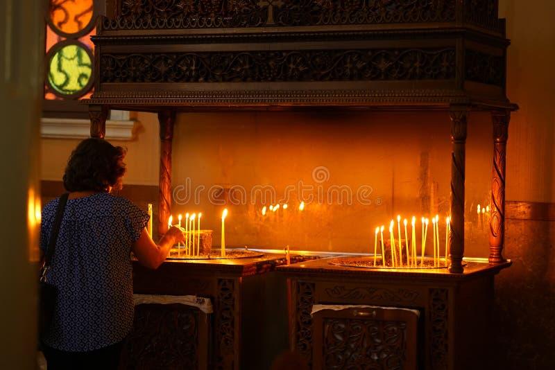 Een persoon steekt kaarsen in de kerk aan stock afbeeldingen