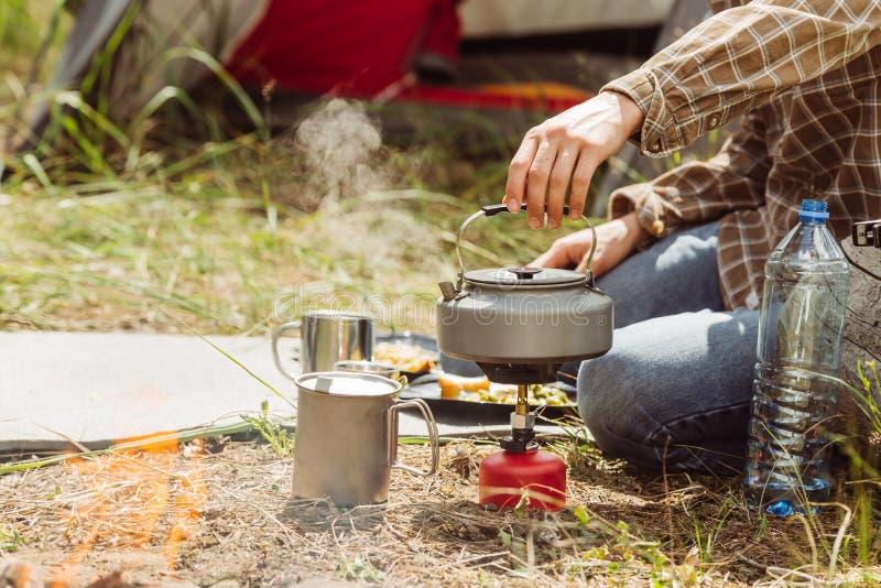 Een persoons kokend water over een propaanfornuis om thee te maken stock afbeeldingen