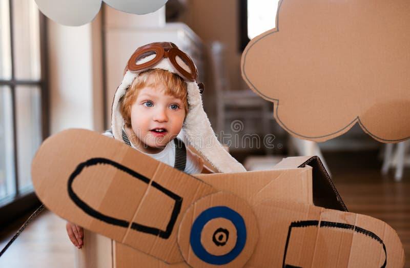 Een peuterjongen met kartonvliegtuig het spelen binnen thuis, het vliegen concept stock foto