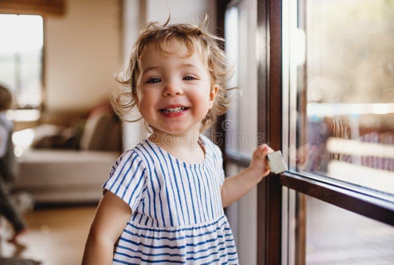 Een peutermeisje die zich binnen thuis door venster bevinden die, camera bekijken royalty-vrije stock afbeeldingen