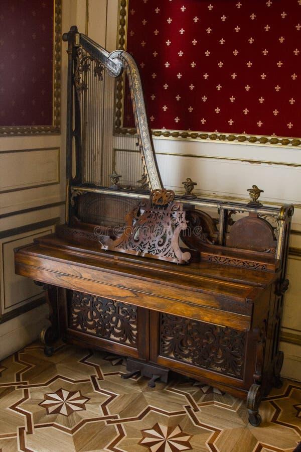 Een piano met een harp bevindt zich in de hoek van een luxeruimte met uitstekend behang barok binnenlands muzikaal instrument royalty-vrije stock fotografie