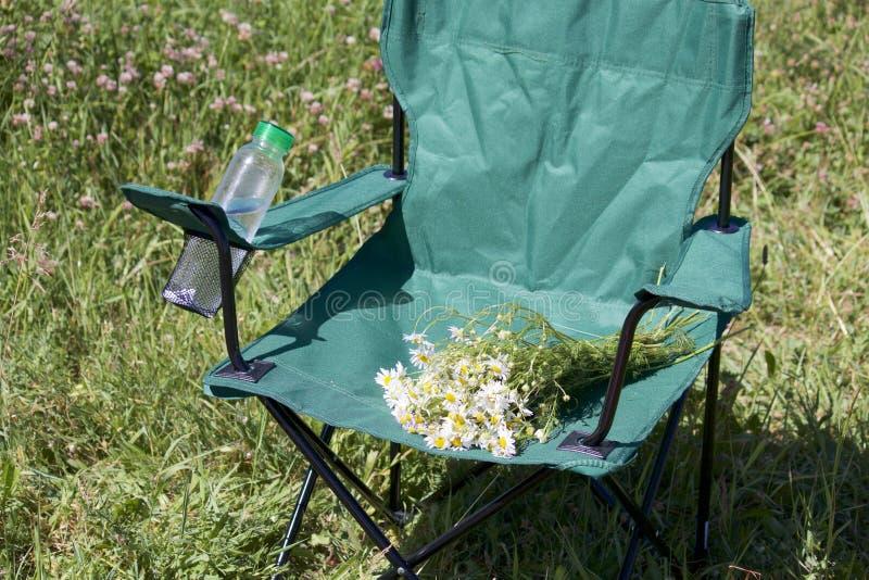 Een picknickstoel bevindt zich op een licht-overstroomde weide In de tribune is een plastic fles water en een boeket van kamilleb royalty-vrije stock foto's