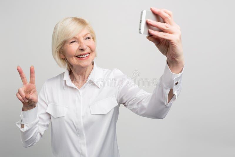 Een picutre vanuit een andere invalshoek waar de oma een selfie neemt Zij kent alles over de jeugd` s tendensen en gebruikt hen royalty-vrije stock afbeelding