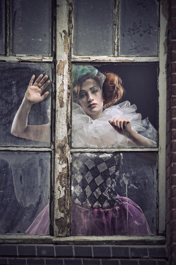 Een pierrotvrouw achter het glas stock afbeeldingen