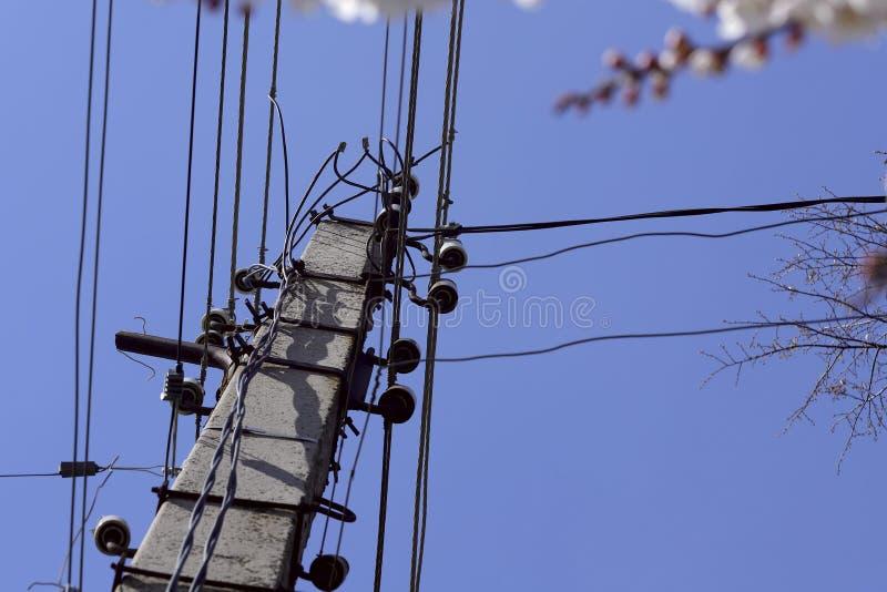 Een pijler met elektrodraden tegen een blauwe hemel stock foto's