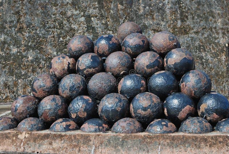 Een piramide van geroeste ijzerballen stock afbeeldingen