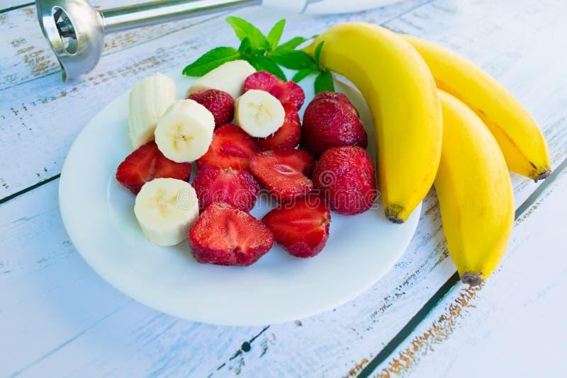 Een plaat met aardbeien en een banaan en een mixer op een witte houten lijst royalty-vrije stock foto