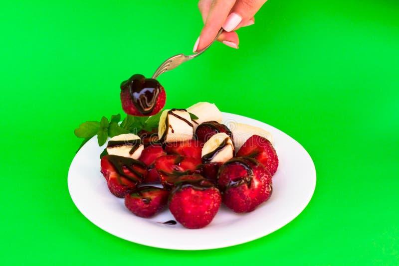 Een plaat met aardbeien en banaan en van een vrouw hand neemt aardbeien op een groene achtergrond royalty-vrije stock foto