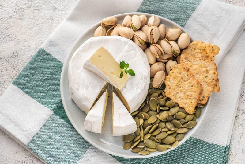Een plaat met Briekaas, pistaches, pompoenzaden Italiaanse antipastisnacks Franse camembertkaas royalty-vrije stock fotografie
