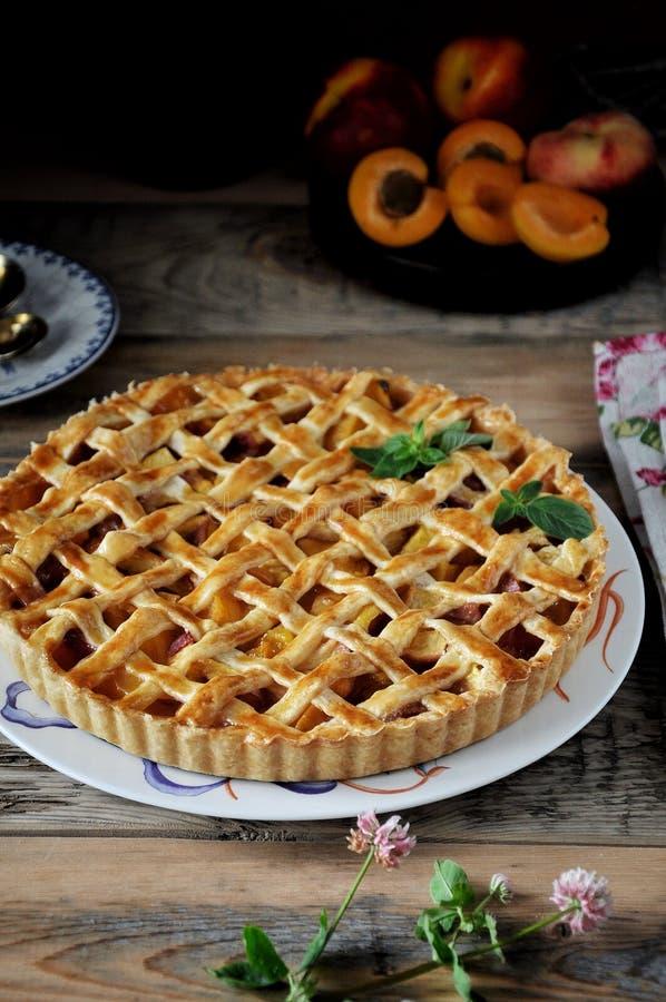Een plaat een pastei met abrikozen close-up stock afbeeldingen