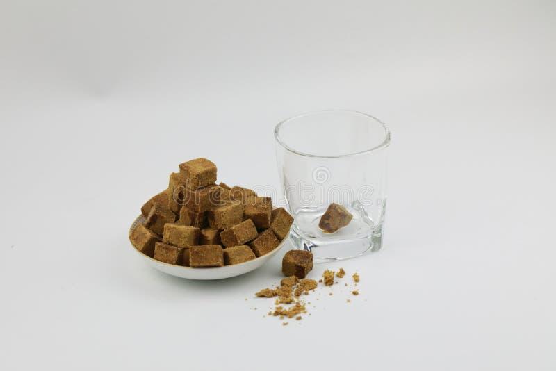 Een plaat van bruine suiker kubeert rotssuiker, het transparante glas van A naast, een stuk van bruine suiker in glas op witte ac royalty-vrije stock fotografie