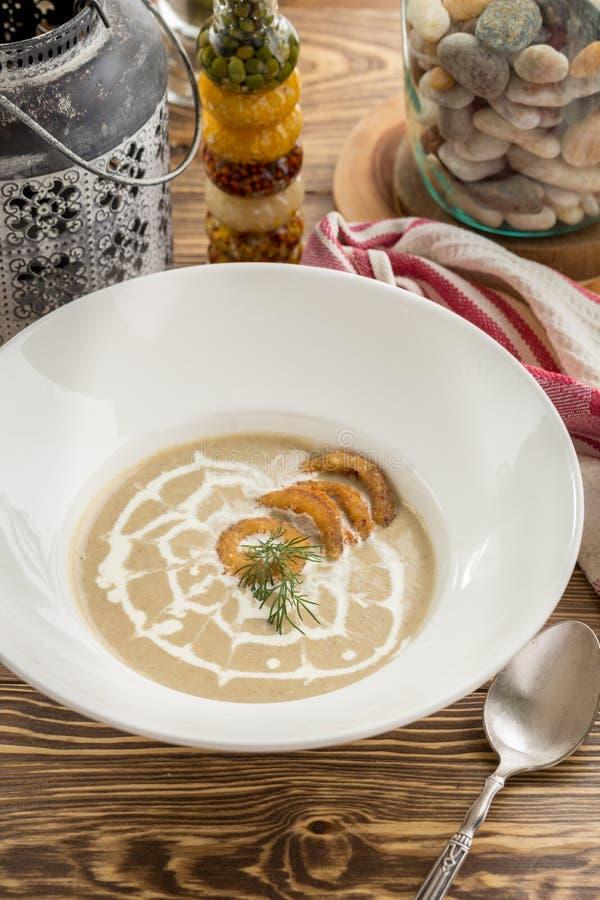 Een plaat van de heerlijke eigengemaakte soep van de paddestoelroom met uiringen op bovenkant op houten lijst royalty-vrije stock afbeeldingen