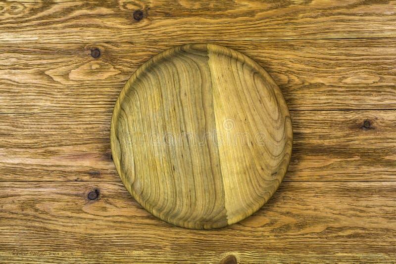 Een plaat van hout ligt op een lichtbruine houten achtergrond royalty-vrije stock fotografie