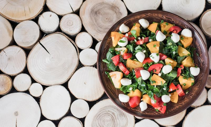 Een plaat van salade met mozarella en groenten op een houten achtergrond stock fotografie