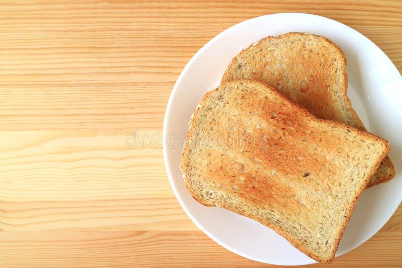 Een plaat van twee stukken van geroosterde gehele die tarwe multigrain sneed brood op houten lijst met beschikbare ruimte voor on stock afbeeldingen