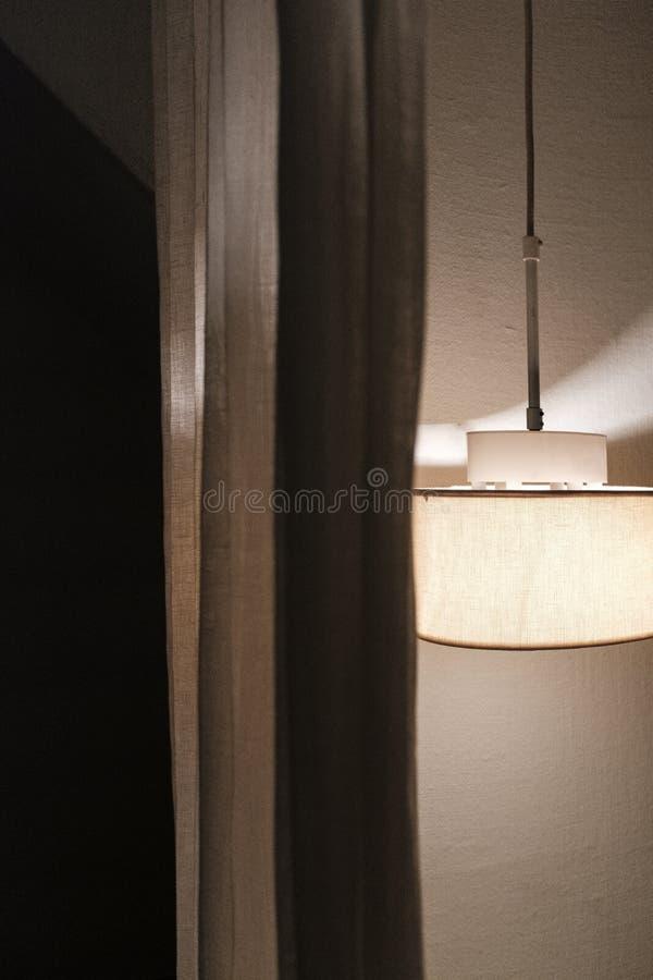 Een plafondlamp naast een gordijn royalty-vrije stock foto