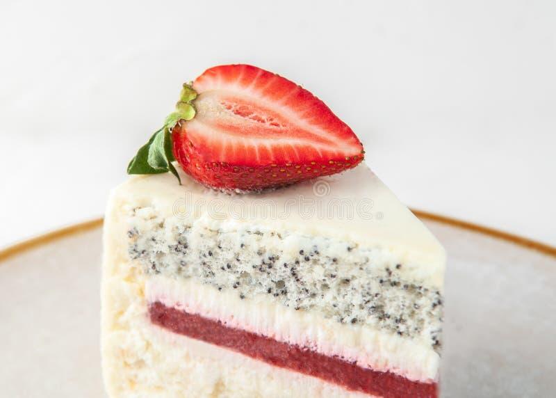 Een plak van aardbeicake op een grijze plaat Verfraaid met aardbeien Close-up Op een witte achtergrond stock foto