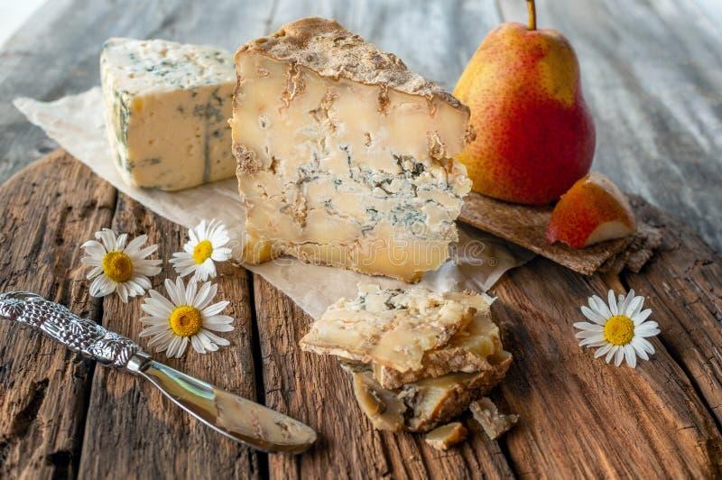 Een plak van blauwe oude Stiltonkaas op een houten lijst De kaas wordt gediend met een mooie rijpe peer De kwaliteit van landbouw stock foto's