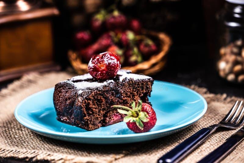 Een plak van brownie met aardbeien op een blauwe plaat royalty-vrije stock foto