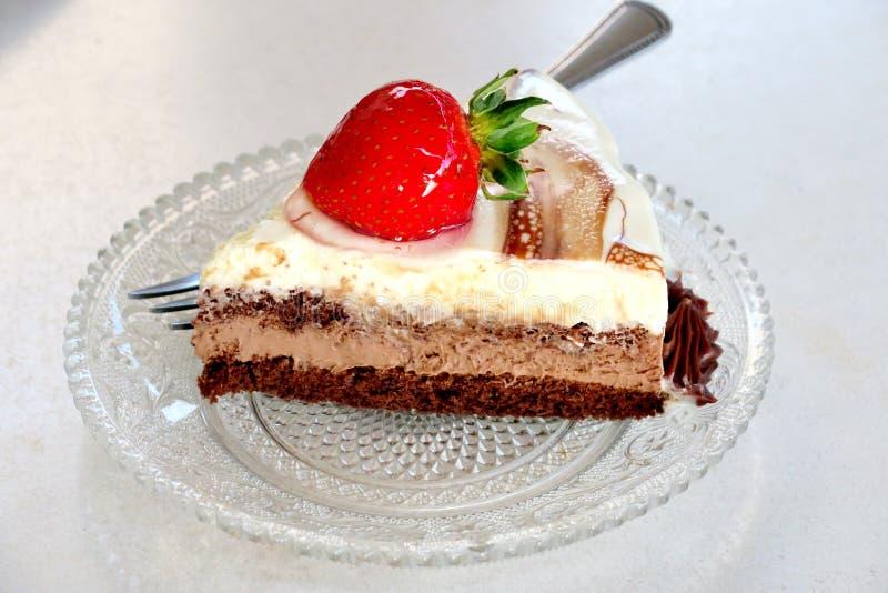 Een plak van cake van drie verschillende lagen met aardbeien op een kleine plaat royalty-vrije stock afbeeldingen