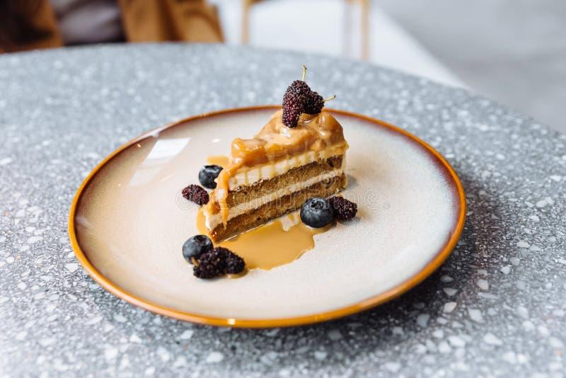 Een plak van de cakebovenste laagje van de koffiekaramel met karamelsaus, bosbes en framboos in plaat in graniet hoogste lijst stock afbeeldingen