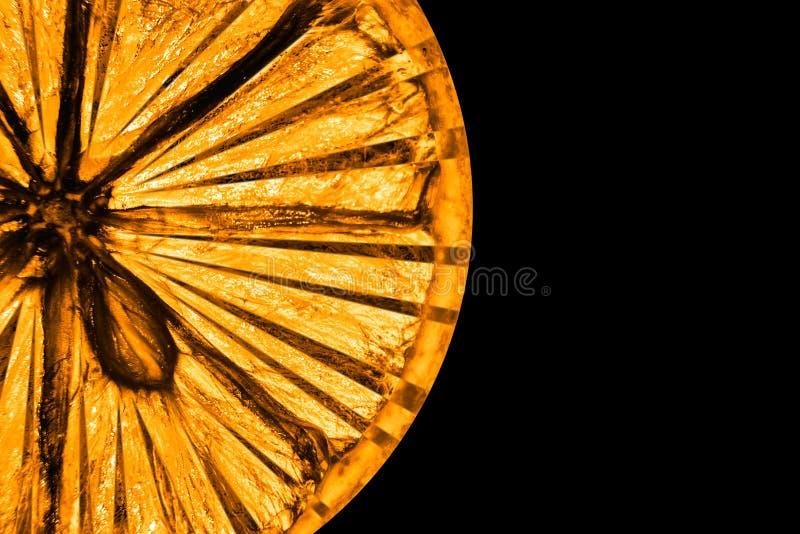 Een plak van droge gele die citroen op een zwarte achtergrond wordt verwerkt en wordt geïsoleerd royalty-vrije stock fotografie