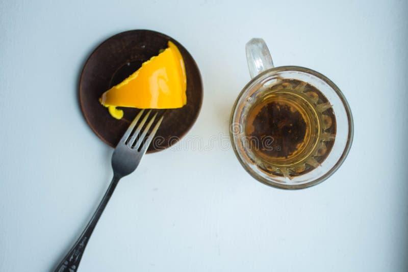 Een plak van heerlijke citroenpastei met thee op een witte achtergrond stock foto