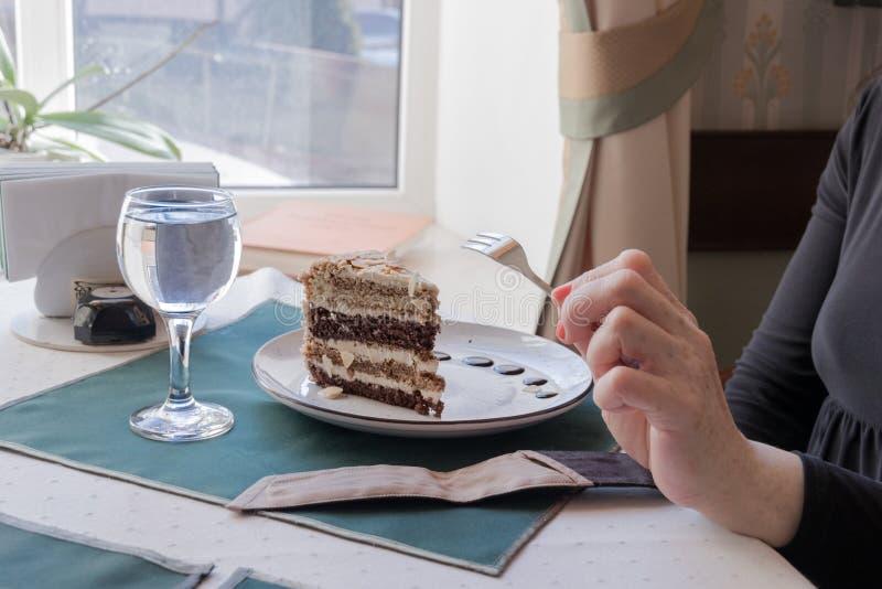 Een plak van multi-layered nootcake in een koffie stock afbeeldingen