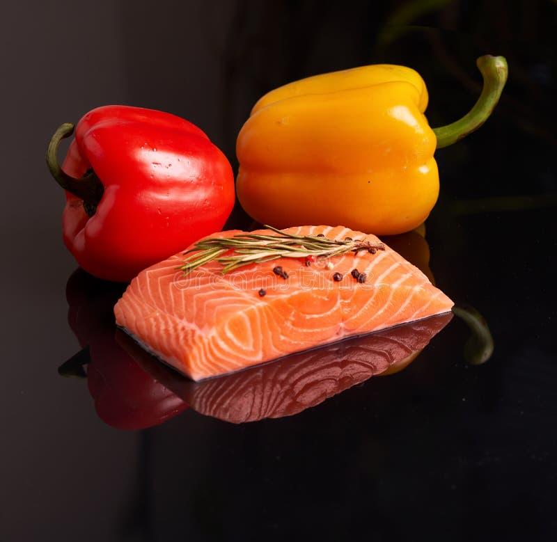 Een plak van ruwe zalmfilet met een twijg van dille op bovenkant en peper met rode en gele paprika op een donkere weerspiegelende stock foto