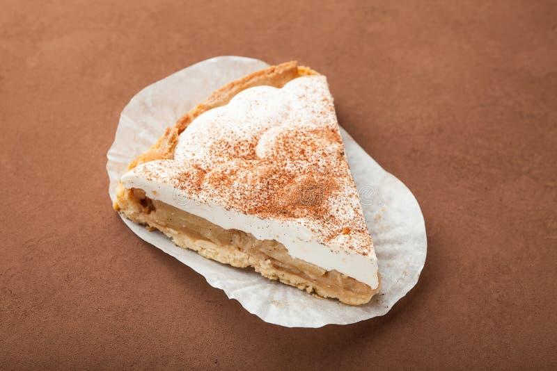 Een plak van smakelijke verse gebakken appeltaart met kaas en room stock foto
