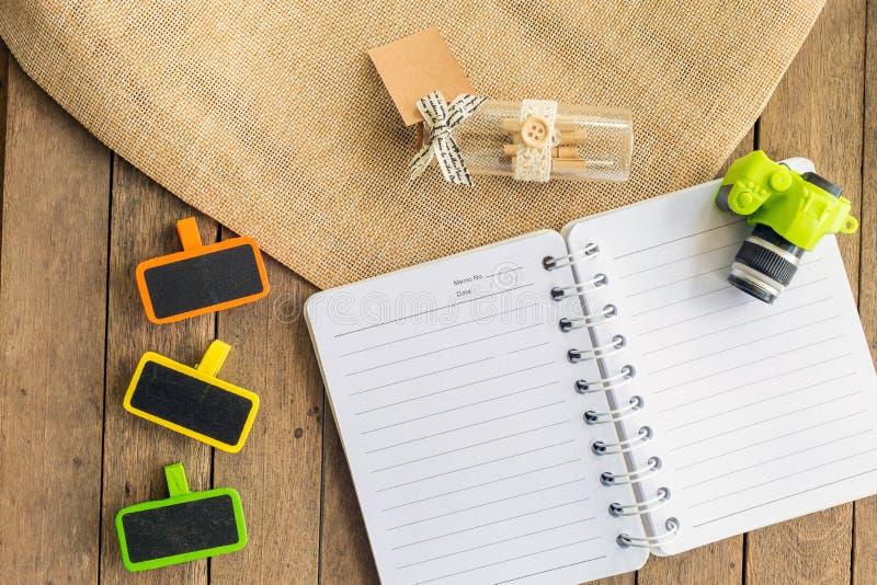 Een planningsboek met een houten markering en toebehoren op houten lijst stock foto's