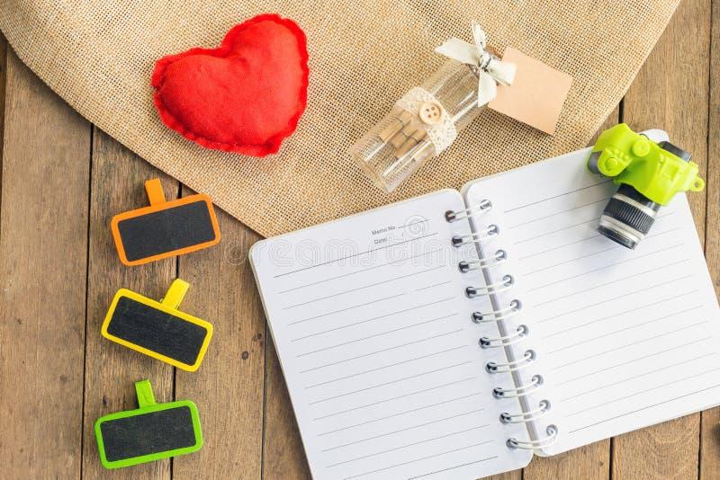 Een planningsboek met een houten markering en toebehoren op houten lijst stock foto