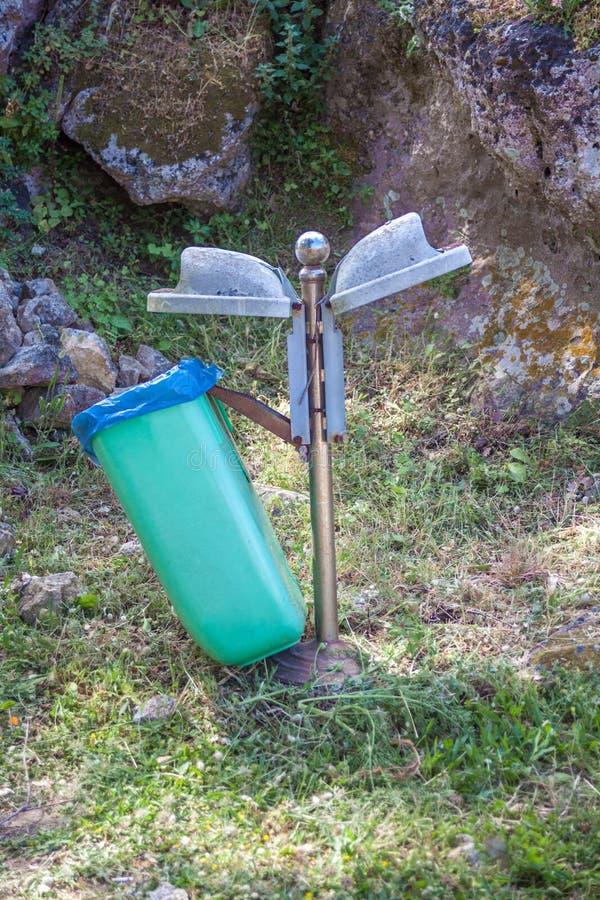 Een plastic afvalbak die zich in de grond bevinden Een metaalpost die de huisvuilcontainer houden Opgestapeld van rotsen die die  stock foto