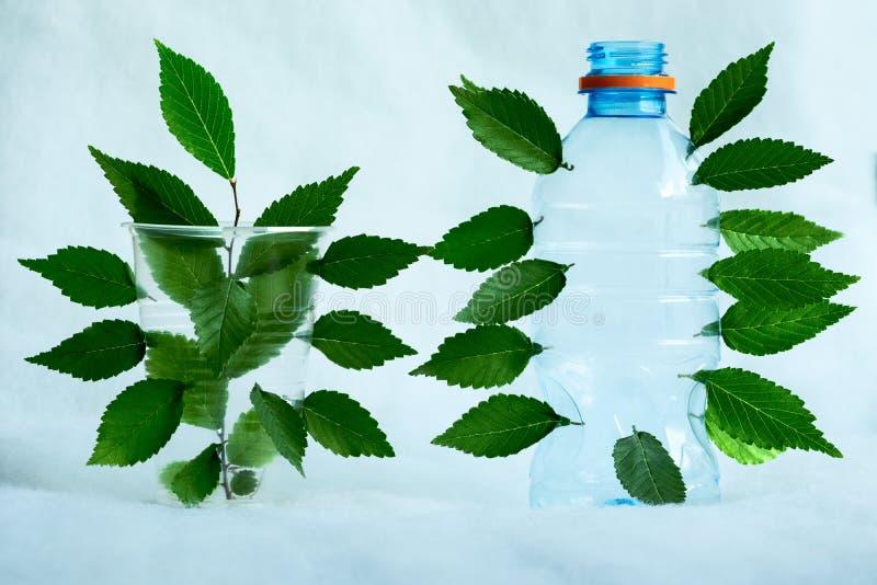 Een plastic fles en een plastic Kop met groen gebladerte ontsproten door hen als symbool van oppositie van milieuvriendelijk stock afbeelding
