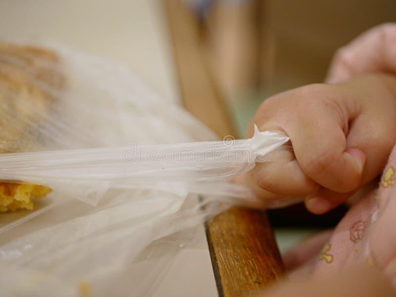 Een plastic zak, met een binnen wafel, hard wordt getrokken door een babyhand stock foto's