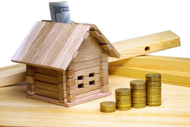 Een plattelandshuisje die zich bij bouwmaterialen en muntstukken bevinden Krediet F stock fotografie