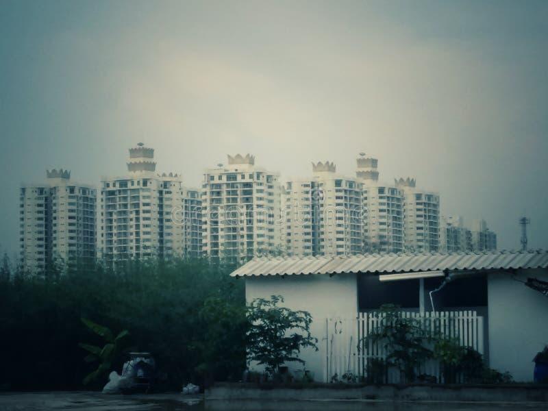 Een plattelandshuisje en een stad of groot flatgebouw royalty-vrije stock foto's
