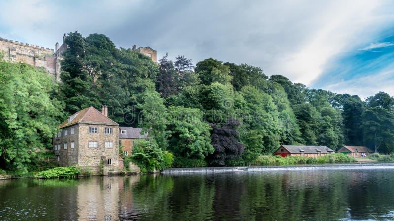 Een plattelandshuisje naast rivier met bomen stock foto