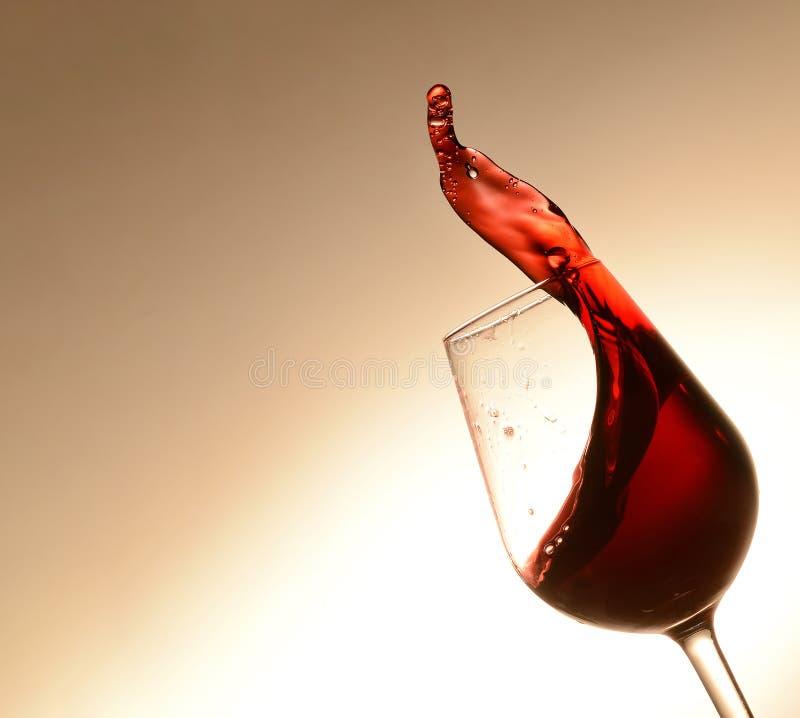Een plons van wijn in een overgeheld wijnglas Robijnrode kleur Een vlotte overgang van licht naar donkerder op de achtergrond stock afbeelding