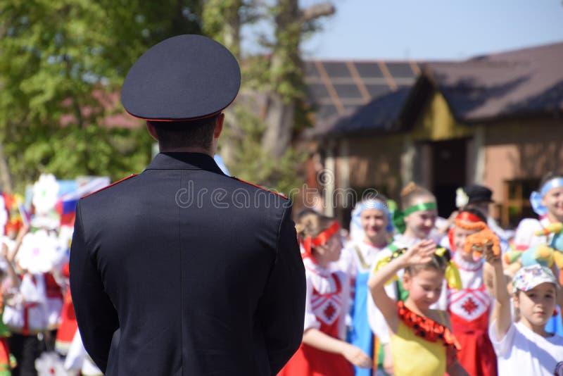 Een politieagent, die de kalmte van burgers bij een feestelijke optocht schreeuwt Het vieren van fir van Mei, de dag van stock fotografie