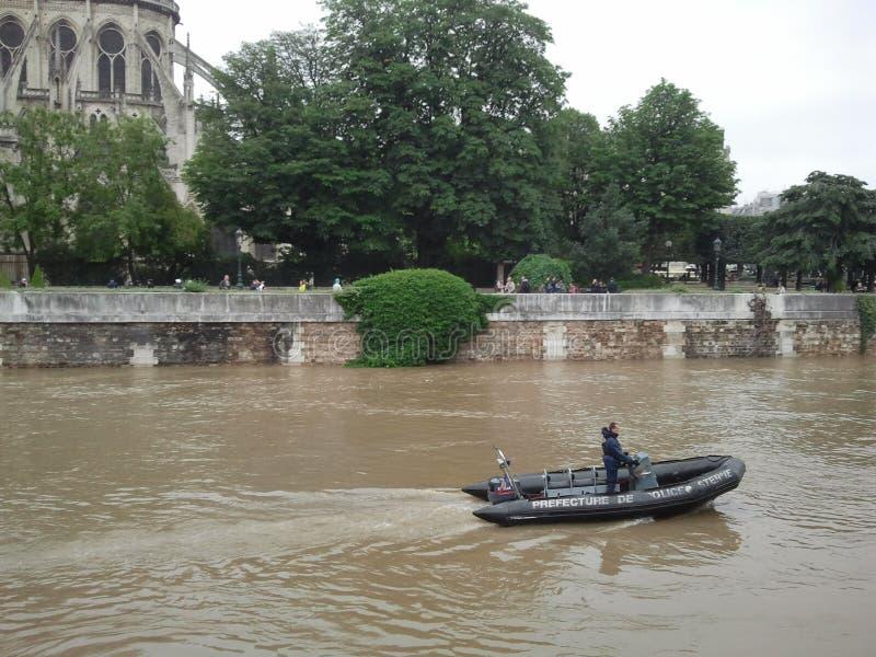 Een politieagent drijft op een boot op een bruine rivier europa frankrijk vloed in Parijs Zegenrivier dichtbij Notre Dame de Pari stock afbeeldingen