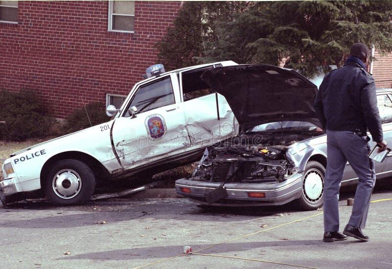 Een politieman bekijkt een autoongeval die een politiewagen impliceren royalty-vrije stock afbeelding