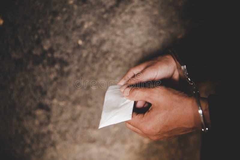 Een politieman vindt drugs tijdens het onderzoek van drugdealers Wet en politieconcept royalty-vrije stock foto