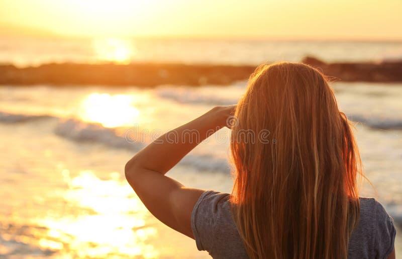 Een portie vrouw kijkt naar zonsondergang over zee, met één hand in de schaduw van haar ogen, kijkt vanuit alleen haar zichtbaar royalty-vrije stock foto's