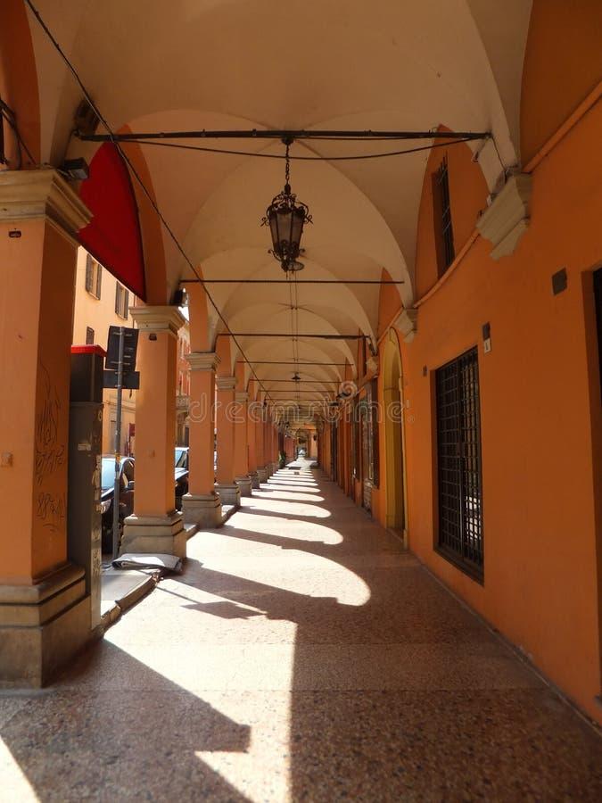 Een portiek in Bologna, Italië Kolommen die tot scherpe schaduwen op de steenbestrating leiden stock afbeelding