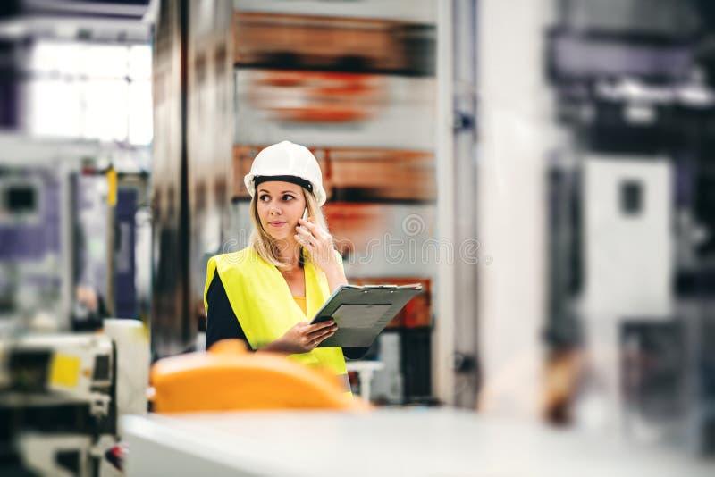 Een portret die van een industriële vrouweningenieur op de telefoon, zich in een fabriek bevinden royalty-vrije stock foto