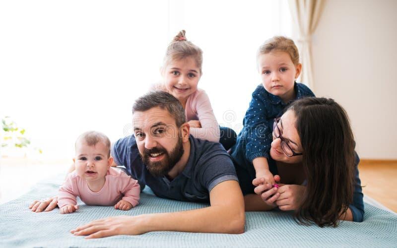 Een portret die van jonge familie met kleine kinderen op vloer binnen liggen stock afbeelding